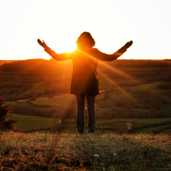 Femme bras levés au coucher de soleil Baulme la Roche